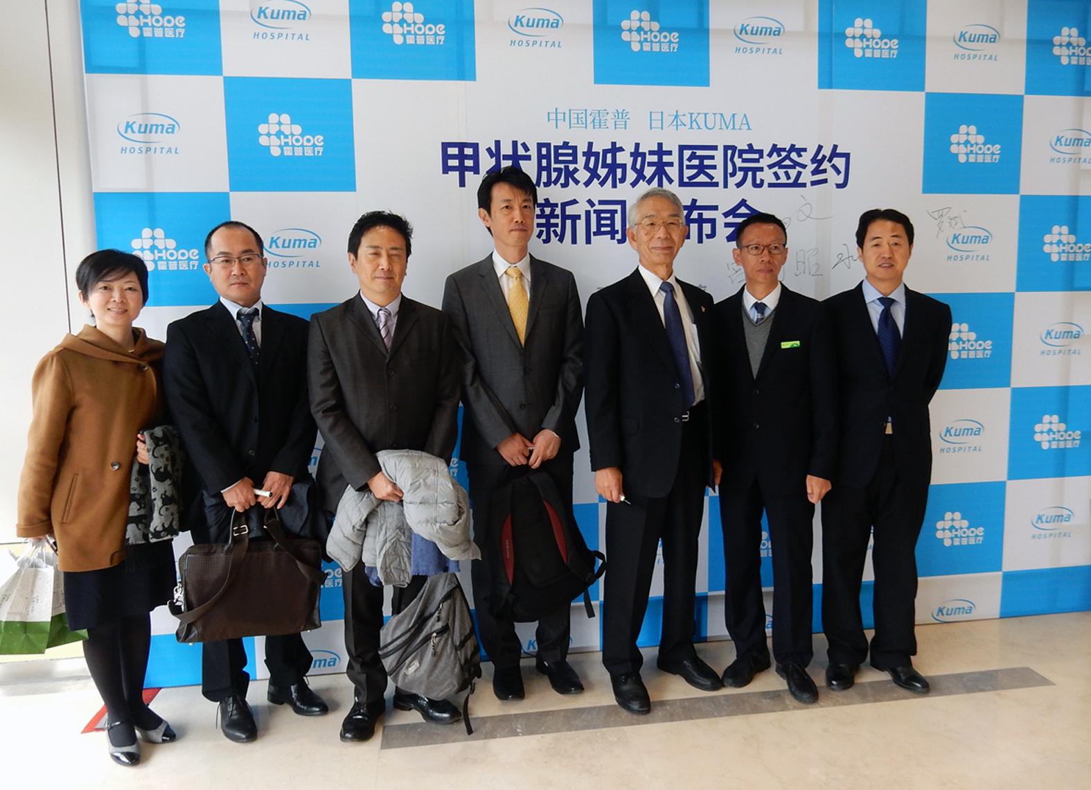 北京Hope Thyroid Hospital訪問団。顔兵院長、姜福亭外科主任(右側の2名)と掲示物の前で記念撮影。